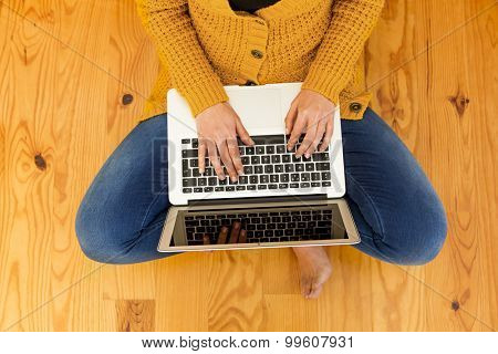 Beautiful woman sitting on the floor working on the laptop
