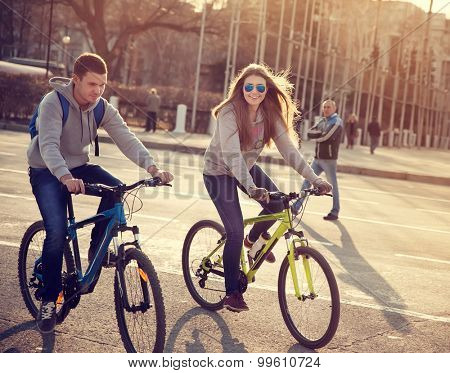 young couple on bicycles in the city at sunset