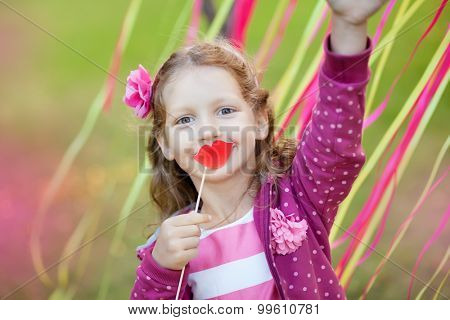 little girl holding paper lips on a stick