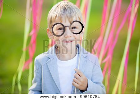 little boy with funny paper glasses