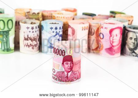 Pile Of Rolled-up Currency Notes With Indonesia Rupiah In Front