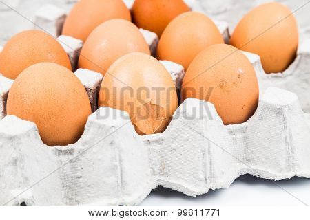 One Egg With Cracked Egg Shell With Other Eggs On Tray.