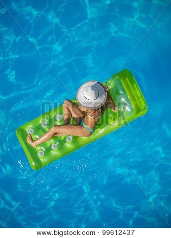 Top view of a  girl on a lilo  in the swimming pool