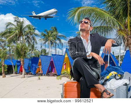 Business man with suitcases at tropical resort in Thailand