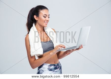 Portrait of a happy fitness woman with towel using laptop computer isolated on a white background