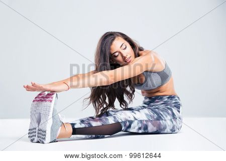 Portrait of beautiful woman stretching on the floor isolated on a white background