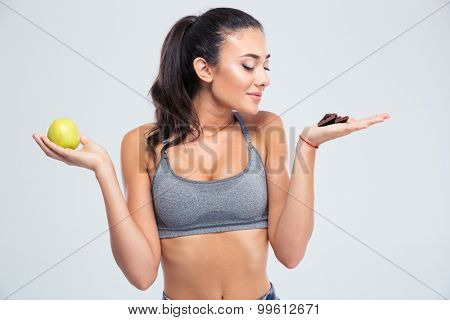 Portrait of a beautiful girl choosing between apple or chocolate isolated on a white background