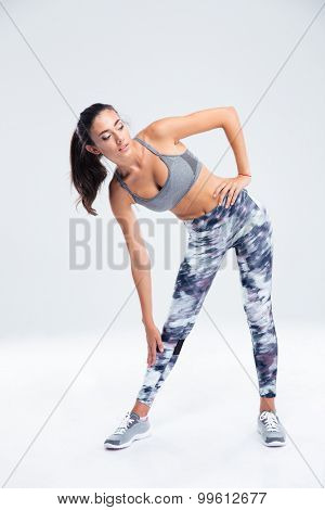 Full length portrait of a sports woman stretching isolated on a white background