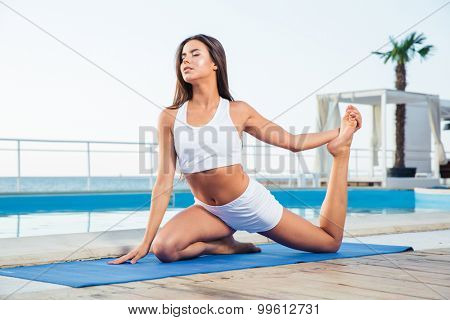 Portrait of a young woman doing yoga exercises outdoors