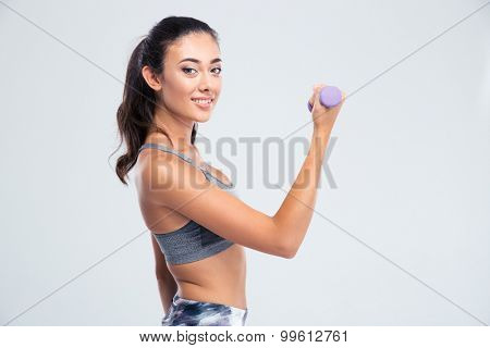 Portrait of a smiling beautiful woman working out with dumbbells isolated on a white background. Looking at camera