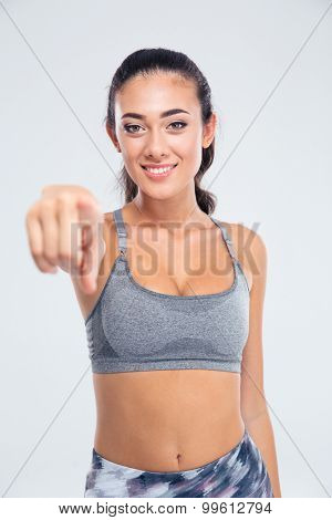 Portrait of a smiling sports woman pointing finger at camera isolated on a white background