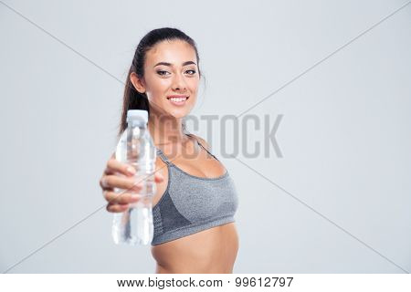 Portrait of a smiling fitness woman holding bottle with water isolated on a white background