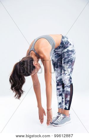 Full length portrait of a fitness woman stretching isolated on a white background