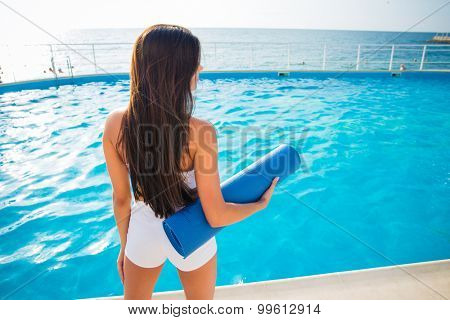 Back view portrait of a young woman holding yoga mat outdoors