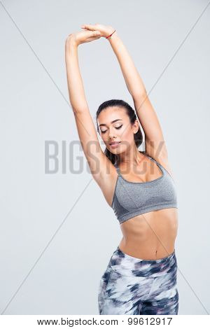 Portrait of a happy fitness woman stretching hands isolated on a white background