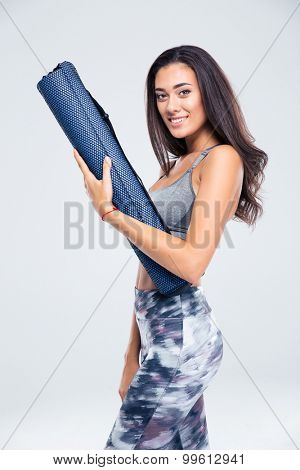 Portrait of a happy fitness woman holding yoga mat isolated on a white background