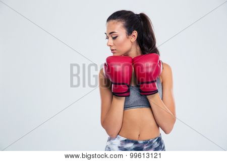 Portrait of a beautiful sports woman standing in defense stance with boxing gloves isolated on a white background