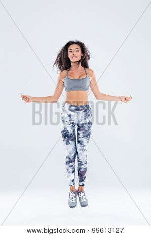 Happy charming woman jumping on skipping rope isolated on a white background
