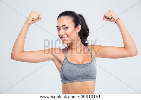 Happy fitness woman showing her biceps isolated on a white background and looking at camera