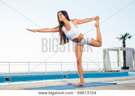 Portrait of a young woman doing stretching exercises outdoors