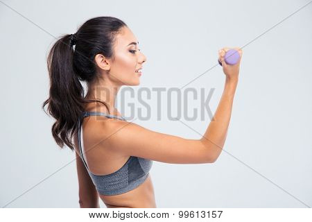 Side view portrait of a happy fitness woman working out with dumbbells isolated on a white background