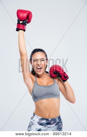 Portrait of a success fitness woman with boxing gloves celebrating her victory isolated on a white backgorund
