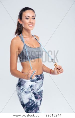 Portrait of a smiling fitness woman with skipping rope isolated on a white background