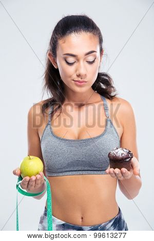 Portrait of a pretty fitness girl choosing between apple and cake isolated on a white background