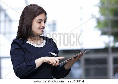 Businesswoman holding a digital tablet at modern office building