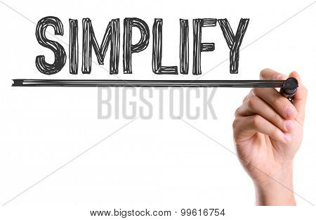 Hand with marker writing the word Simplify