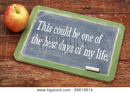 This could be one of the best days of my life - positive affirmation phrase on a slate blackboard with a white chalk and a stack of books against rustic wooden table
