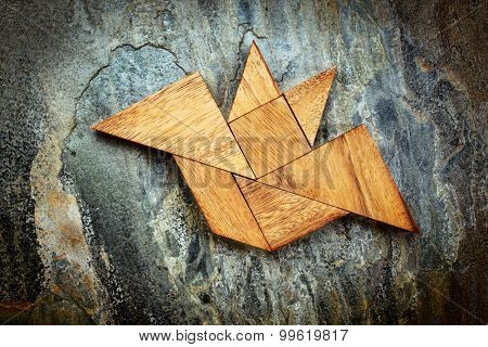 abstract picture of a flying bat built from seven tangram wooden pieces over a slate rock background, Halloween concept, artwork created by the photographer