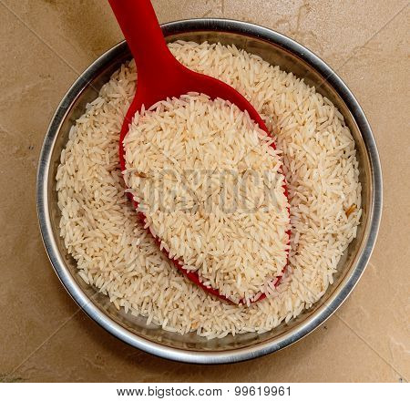 Long grain basmati scented rice kept in a bowl on a plain background
