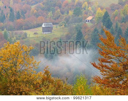 Mountain village with wooden houses. Autumn Landscape with deciduous forest on the slopes. Carpathians, Ukraine, Europe