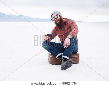 beard hipster with smart phone and suit case in the salt flats looking for directions with copyspace composition
