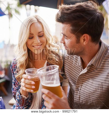 romantic couple drinking beer in outdoor pub or bar making a toast