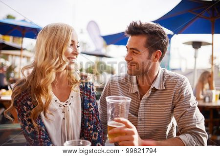 couple drinking beer in beach side outdoor pub or bar together