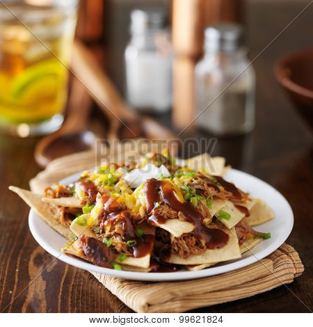 barbecue pulled pork nachos with sour cream, green onions and melted cheese