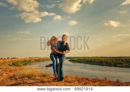 Loving Couple Hugging On Bank Of River.