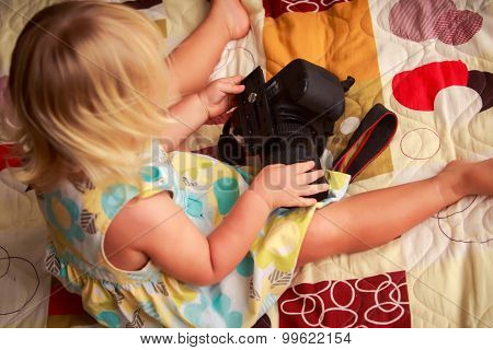 Little Blonde Girl Backside View Examines Camera On Sofa