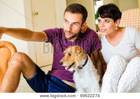 Man and woman in they house playing with the dog