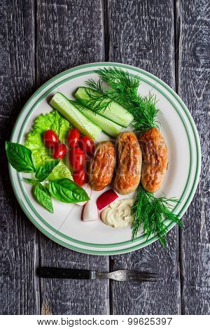 Roasted sausages and vegetables on the plate over wooden background