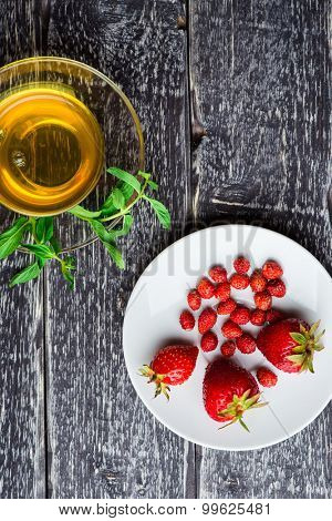 A cup of herbal tea with fresh mint and ripe strawberry on wooden background