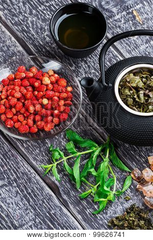 Black iron asian tea set with fresh mint and ripe strawberry on wooden background