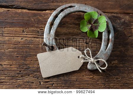 St. Patricks day, lucky charms. Four leaved clover and a horseshoe on wooden board