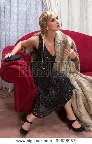 Charleston lady in a flapper dress sitting on a luxury chaise longue