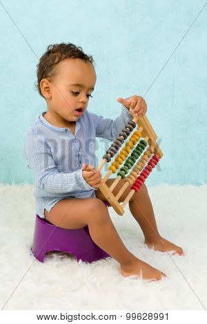 Potty training of a cute African toddler boy playing with an abacus