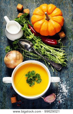 Pumpkin soup  with fresh ingredients on wooden board
