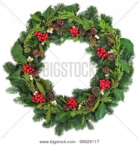 Christmas wreath with holly, ivy, mistletoe and winter greenery over white background.