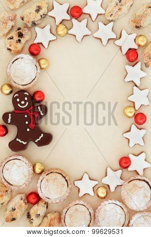 Abstract christmas background border with stollen, mince pie cakes, gingerbread biscuits and foil wrapped chocolate balls  on parchment paper.